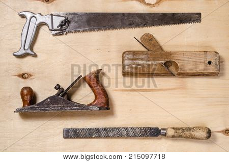 a set of tools for working on a timber - saw plane jointer rasp - lay on a sheet of plywood. flat view.
