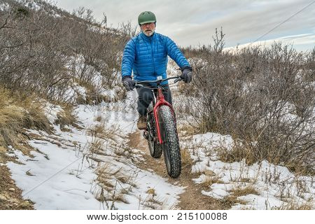 a senior male riding a fat bike on Cheyenne Rim in Red Mountain Open Space, late fall or winter scenery with some snow