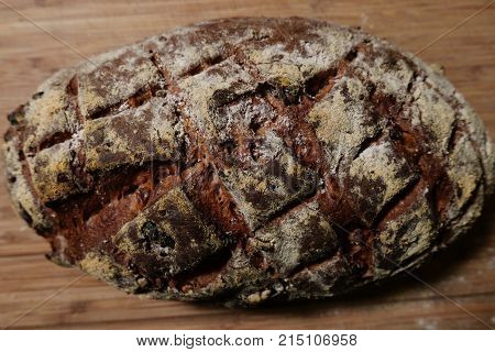 Loaf of walnut bread showing cross hatch slash marks in the dark crust and the dusting of flour.