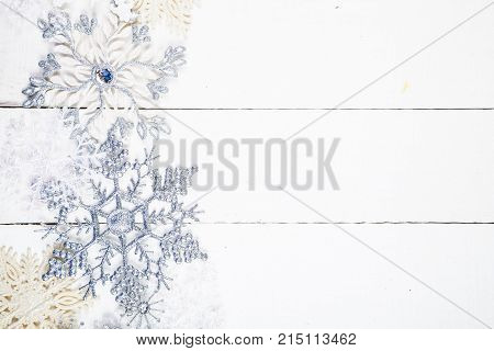 Silvery Snowflakes On A Wooden Background