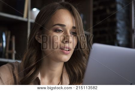 She beautiful at work. Young businesswoman sitting in cozy office and with concerned expression on face looking at laptop screen. Business in cozy dark studio