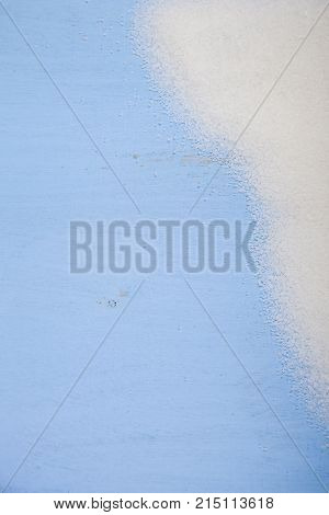 White sugar on blue wooden background ,