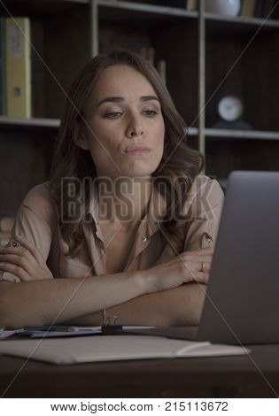 Thoughts in her head. Young beautiful business woman sitting in office at table with gray laptop with pensive expression on face and clasped hands together. Creative start up in cozy dark studio