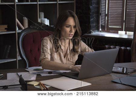 Persistence and work. Young businesswoman working very hard with laptop sitting in office chair behind desk on which various documents and tablet. Creative start up business in office