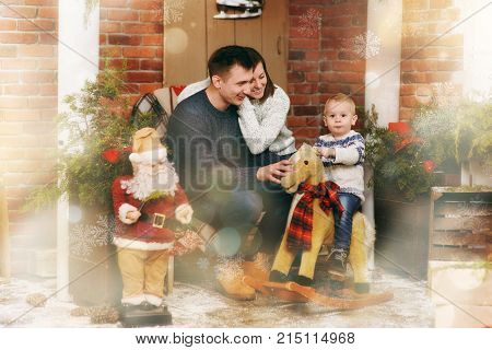 Young Happy Parents With Little Child Son On Rocking Horse In Decorated New Year Room With Santa At