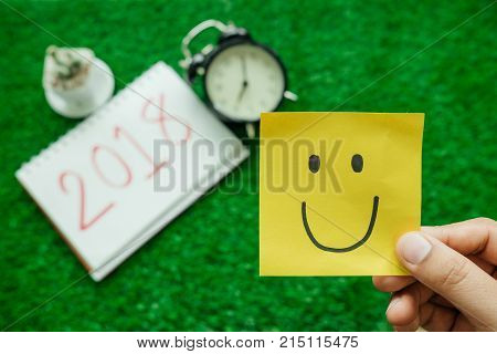Happy New Year Background With Smile Note Paper, Clock, Plants And Notebook Has Message 2018 Isolate
