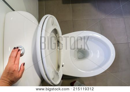 close up woman left hand flush the toilet for hygiene