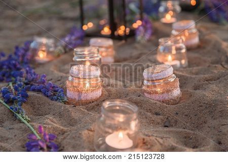 Beautiful decorated romantic place for a date with jars full of candles hanging on tree and standing on a sand.