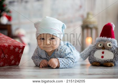 Cute Christmas Portrait Of Little Baby Boy, Lying On His Belly On The Floor, Smiling Happily