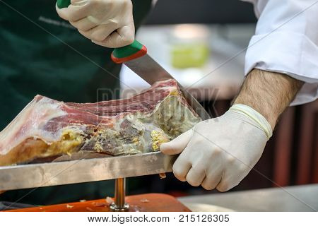 Cutting slices of cured iberian ham .