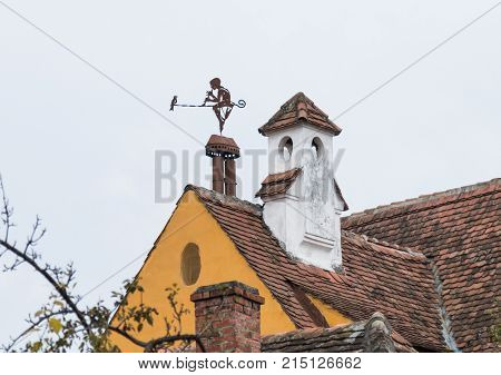 Sighisoara Romania October 08 2017 : Weathervane in the form of a boy with a pipe and a bird on the roof of a dwelling house in the old city of Sighisoara in Romania