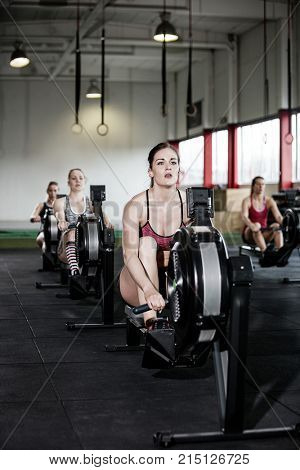 Young Women Exercising On Rowing Machines