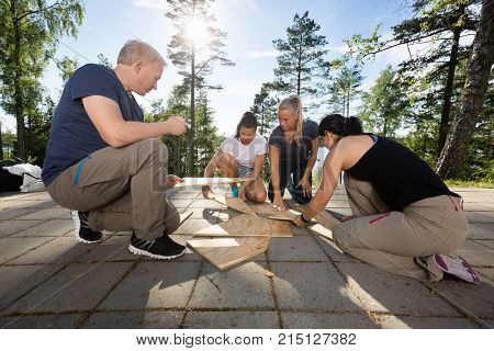 Coworkers Solving Wooden Plank Puzzle On Patio