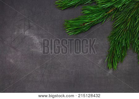Christmas And New Year Greeting Card With Spruce Tree Brunches Frame And Copy Space On Black Chalkbo
