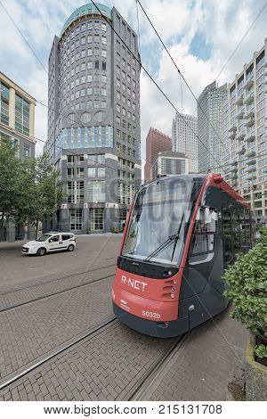 The Hague 25 August 2017 - Red and black tram running toward the city center of The Hague passing inside the private home building