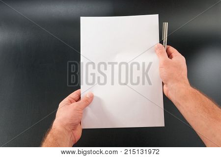 Man's Hands With Paper On A Black Background. Studio Isolate.