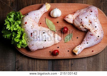 A flavored raw chicken thigh on a wooden surface. Chicken drumstick before preparation. Dietary meat on the table. Still-life from a raw chicken leg.
