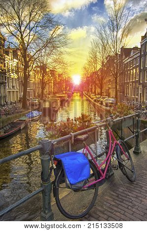 Beautiful spring sunrise view of Amsterdam canal along the bridge where Amsterdamers used to park their bicycle Netherlands