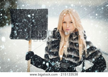Woman Standing With Snow Shovel In Hand On Winter Day