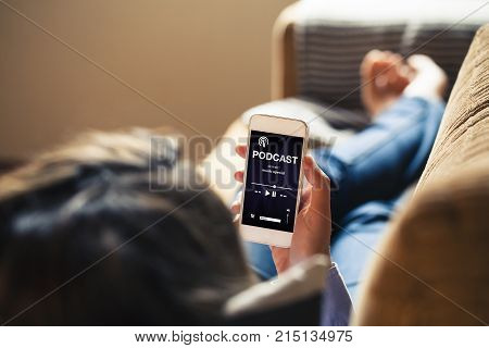 Woman listening podcast in a mobile phone while lies down on a sofa at home.