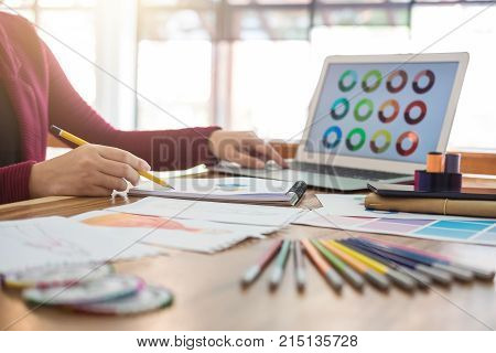 Close up of woman fashion designer at work drawing sketches for clothes in atelier with tailor tool and color charts profession and job occupation Fashion Designer Stylish Concept.