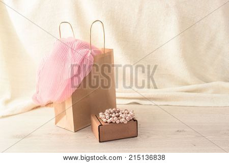 Set of shopping for women in Kraft packaging. Pink scarf in your bag for shopping pearl bracelet on top of the box. Fashion accessories