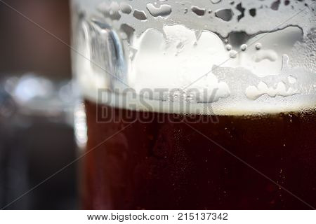 Close-Up Of Refreshing Cold Pint Of Dark Ale Beer With Condensation, Frothy Foam And Bubbles Ready To Drink