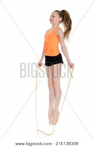 A girl gymnast performs exercises with a skipping rope.A girl gymnast performs exercises with a skipping rope. The concept of a healthy lifestyle, sports education of a child, Happy childhood. Isolated on white background.
