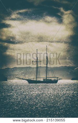Old wooden ship in the sea under a dramatic sky.Fine art image canvas texture added.