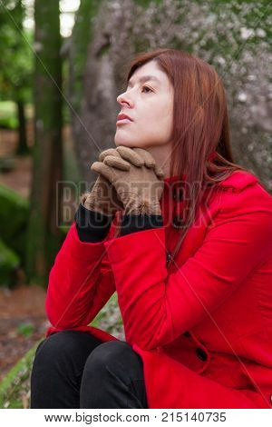 Depressed and sad young woman feeling depression sitting on forest, looking up with melancholic thinking, wearing a red long coat or overcoat during fall, autumn or winter