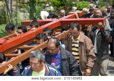 March 25, 2016 San Pedro la Laguna, Guatemala: mayan men carrying a wooden cross during Easter procession