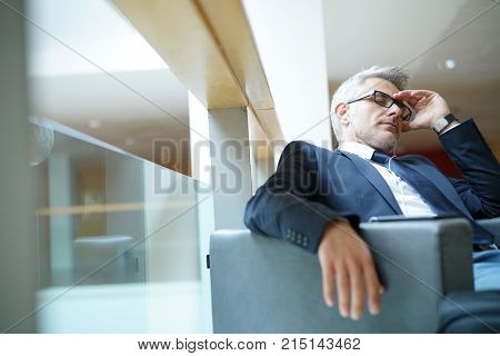 Businessman taking a nap in airport departure lounge