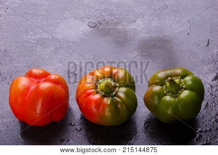 Appetizing, juicy, Bulgarian pepper, decomposed orange and green, mature, and half-ripe, on a black background. Top view, free space for text.