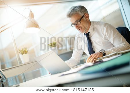 Businessman in office working on laptop computer