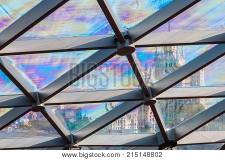 glass roof of the building with views of the skyscraper through the glass. focus on the skyscraper