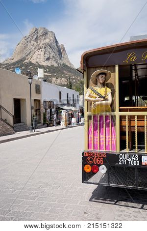February 26, 2016 Bernal Mexico: tourist bus with the Bernal monolith in the background, the third largest monolith in the world