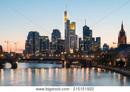 View of Frankfurt am Main skyline at dusk along Main river with cruise ship in Frankfurt Germany