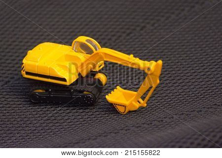 Yellow excavator on a blurred black background. Buiding machinery. Children's toy car.