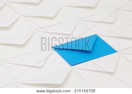 Composition with white envelopes and one blue envelope on the table.