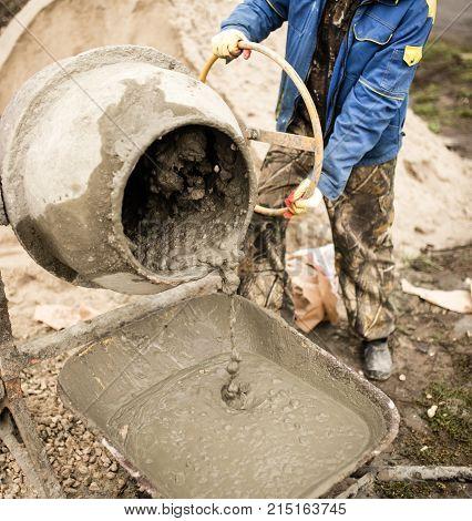 worker pours concrete mortar on a construction site .