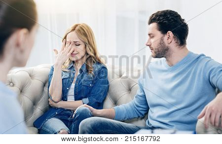 I cant stand it. Cheerless upset young woman covering her face and crying while sitting together with her husband at the psychologists office