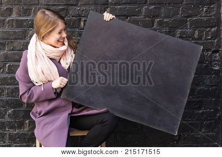 fashion, femininity, advertisment concept. in front of black brick wall there is adorable loughing woman that is holding blackboard for drawing with colorful chalks