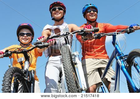 Portrait of happy family on bicycles against blue sky