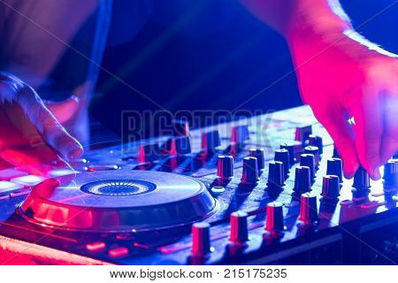 Motionblur of Dj hands on equipment deck and mixer with vinyl record at party.Closeup.