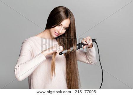 Beautiful woman curling long hair using curling iron.