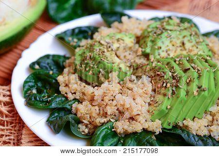 Quinoa with spinach and avocado. Spicy quinoa spinach avocado salad on a white plate. Closeup