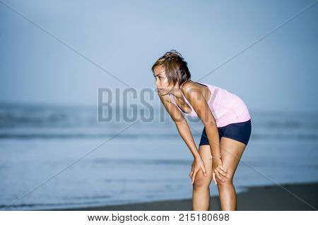 young attractive and fit Asian sport runner woman cooling off breathing after running on beach sea side looking tired while hard workout in fitness body care and healthy lifestyle concept