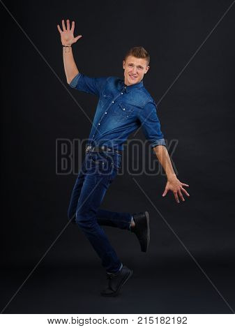 The guy is handsome, young, stylish in jeans and a denim shirt is standing on one leg and raised one hand up a friend down on a black background