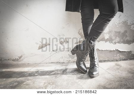 A woman legs wearing black boots with high heel. Black and white tnoe.