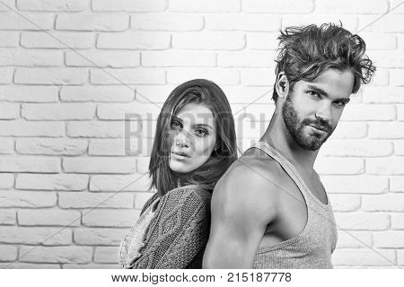 Young couple of handsome man or muscular macho in grey undershirt with pretty cute girl or beautiful woman in knitted coat on white brick background
